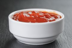 White bowl with tomato sauce on slate board Royalty Free Stock Image