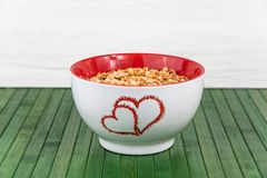 A white bowl with two hearts roasted on it full of granola on gr. Een wood table stock images