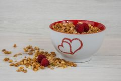 A white bowl with two hearts roasted on it full of granola whit. Berries on white wood table stock photos