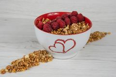 A white bowl with two hearts roasted on it full of granola whit. Berries on white wood table royalty free stock images