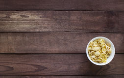 White bowl wit yellow corn flakes on wooden background Stock Photography