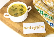 White bowl with yellow chicken soup with green dill with a note `secret ingredient` stock photo