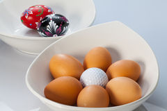 White bowls, easter eggs and golf balls Royalty Free Stock Images