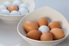 White bowls, easter eggs and golf balls Stock Photo