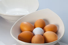 White bowls, easter eggs and golf balls Stock Photography