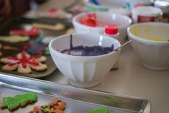 White bowls of frosting next to decorated Christmas cookies royalty free stock images