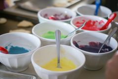 White bowls of multiple frosting colors used to decorate stock images