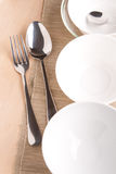 White bowls and silverware on napkin and wood Stock Photography