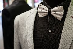 White bowtie with black dots, on display with a black shirt and a white wool suit jacket. Bow ties are a symbol of elegance and st. Picture of a white bowtie stock photo