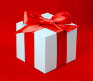 White box, bow and ribbon. On red background Royalty Free Stock Image