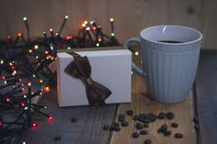 Gift box with bow, blue cup, lights, on Christmas tablenn Royalty Free Stock Photography