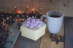 White gift box, blue cup, coffee beans on the tablennn Royalty Free Stock Images