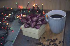 Gift box, blue cup, lights, coffee beans on the tablennn Stock Photo