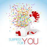 White box with red ribbon and colorful confetti an Stock Photos