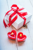 White box with red ribbon, red candles in the shape of heart. Ro. White box with red ribbon and red candles Royalty Free Stock Image