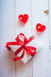 White box with red ribbon, red candles in the shape of heart. Ro. White box with red ribbon and red candles Stock Images