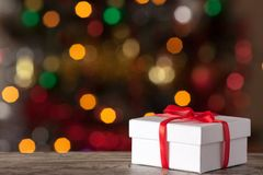 White box with a ribbon on a background bokeh.  Stock Image