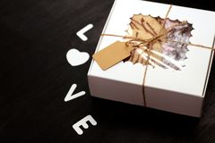 White box with a transparent cover, tied with a rope, with cookies and a label for text on a dark background. A gift for Valentine royalty free stock photography