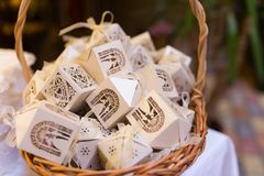 White boxes for guest attending the wedding in the basket. Shaped favors the house that contain confetti. Bonbonniere for guests Stock Photography