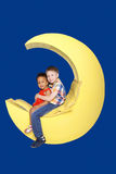 White boy and black girl sitting on the moon. Royalty Free Stock Photo
