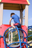 White boy climbing on playground Stock Image