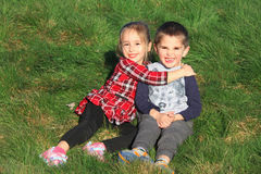 White boy - girl twins sitting on green grass royalty free stock photo