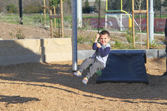 White boy riding zip line in the park Stock Photos