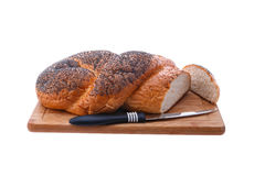 White bread, braided on a cutting board. And table knife Royalty Free Stock Images