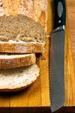 White bread and knife on wooden cutting board Stock Photo