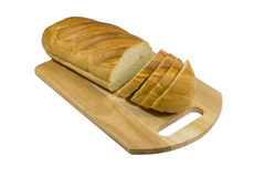 White bread lays on a chopping board. White bread is cut on pieces. On a white background Stock Photo