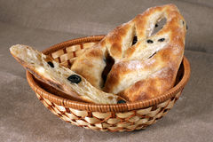 White bread stuffed with olives lies in a straw basket on gray l Stock Photography