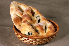 White bread stuffed with olives lies in a straw basket on gray l Stock Image