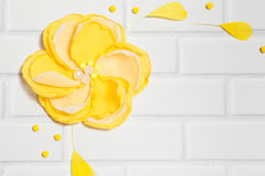 White Brick Background With Big Handmade Yellow Flower Stock Photo