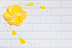 White Brick Background With Handmade Yellow Flower Stock Photos