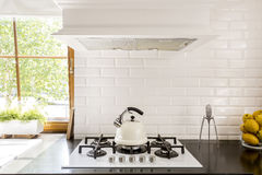 White brick backsplash idea. New style kitchen with dark worktop, white gas cooker and decorative brick backsplash stock photos