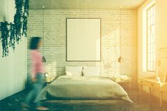 White brick bedroom, poster toned. White brick bedroom interior with a wooden floor, a large window, a gray bed and two bedside tables. A cabinet with mirrors. A Royalty Free Stock Photography