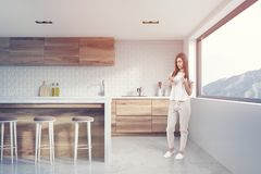 White brick kitchen interior, side view toned. White brick kitchen interior with a concrete floor, wooden countertops and a large window with a perfect view. A Stock Image