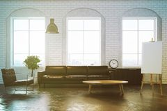 White brick living room, brown sofa toned. White brick living room interior with a leather sofa and armchair, a coffee table and an easel with a blank canvas on Stock Image