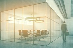 White brick meeting room corner, man. Businessman in a white brick conference room interior with a concrete floor, glass walls and a long table with black chairs Royalty Free Stock Photo