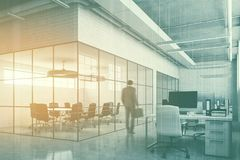 White brick meeting room in open space, man. Businessman in a white brick conference room interior with a concrete floor, glass walls, a long table with black Royalty Free Stock Photo