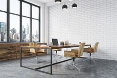 White brick open space office interior. Meeting room interior with white brick walls, a concrete floor, large windows and a long wooden table with wooden chairs Royalty Free Stock Photos