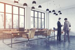 White brick open space office toned. Conference room corner with white brick walls, a concrete floor, large windows and a long wooden table with wooden chairs Stock Photography