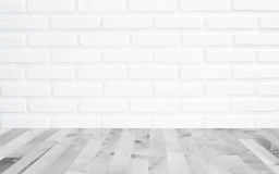 White brick wall background with perspective light wood, slightly blurry wood foreground