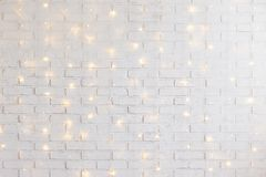 White brick wall background with shiny lights. White brick wall christmas background with shiny lights royalty free stock photography