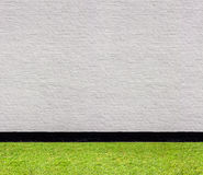 White brick wall with black horizontal seamless pattern and lawn Royalty Free Stock Images