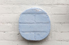 White brick wall with blue circle in the center Royalty Free Stock Photography