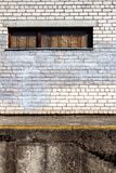 White brick wall with a boarded window. Building structures, abandoned building, window with shot marks royalty free stock images