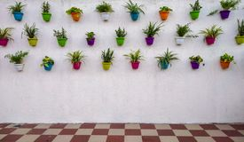 white brick wall with colorful plants and pots hanging on it stock photo