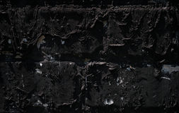 A white brick wall covered by layer of black bitumen. Royalty Free Stock Photography