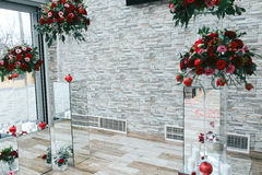 White brick wall decorated with red bouquets and glass boxes in Royalty Free Stock Images